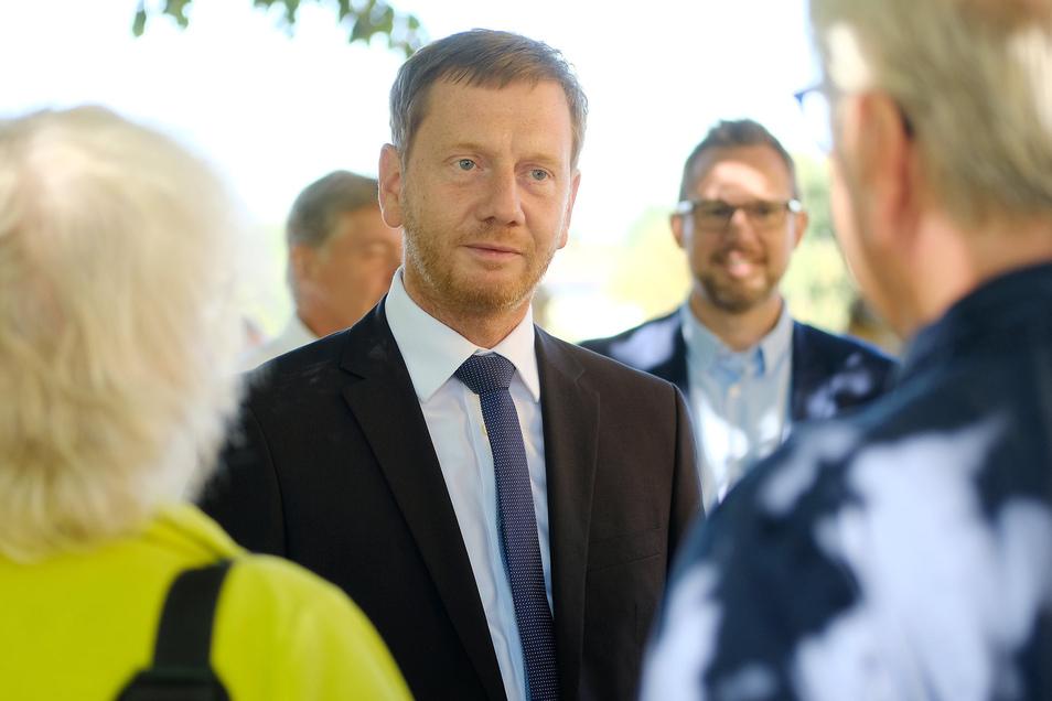 Bei der Tour durch Klipphausen spricht Ministerpräsident Michael Kretschmer mit den Menschen in einer Kirche.