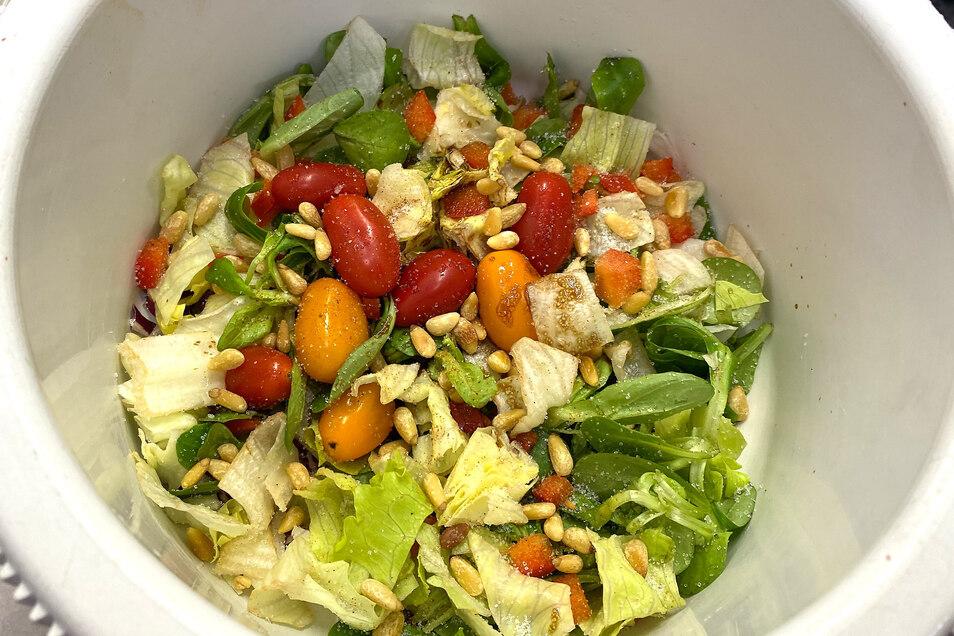 Für den Salat Radicchio, Feld- und Eisbergsalat und Paprika schneiden. Zwei Esslöffel Olivenöl mit einem Esslöffel dunklem Balsamicoessig mischen, Mit Salz, Pfeffer und etwas Zucker abschmecken und gemeinsam mit kleinen Tomaten, gerösteten Pinienkernen und ein wenig Parmesankäse zum Salat geben.