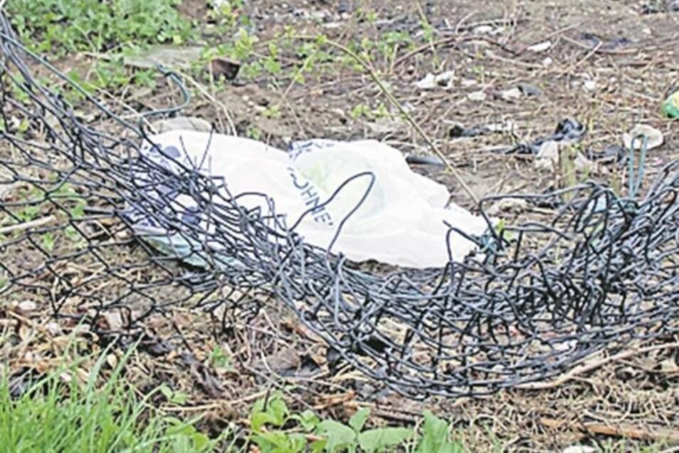 Stadtrandsiedlung: Müllbeutel fliegen immer wieder über den defekten Maschendrahtzaun. Zweimal im Jahr räumt der Bauhof den Dreck weg.