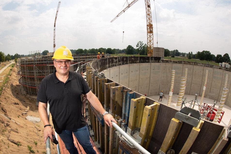 Projektleiter Mirco Helbig vor dem Rohbau eines Silos. Darin können 2.000 Kubikmeter Schlamm gespeichert werden, die bei der Vorreinigung anfallen.