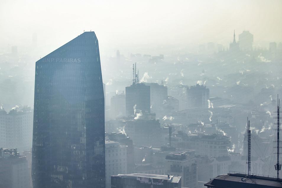 Weißer nebliger Rauch aus Schornsteinen hängt über der Innenstadt von Mailand.
