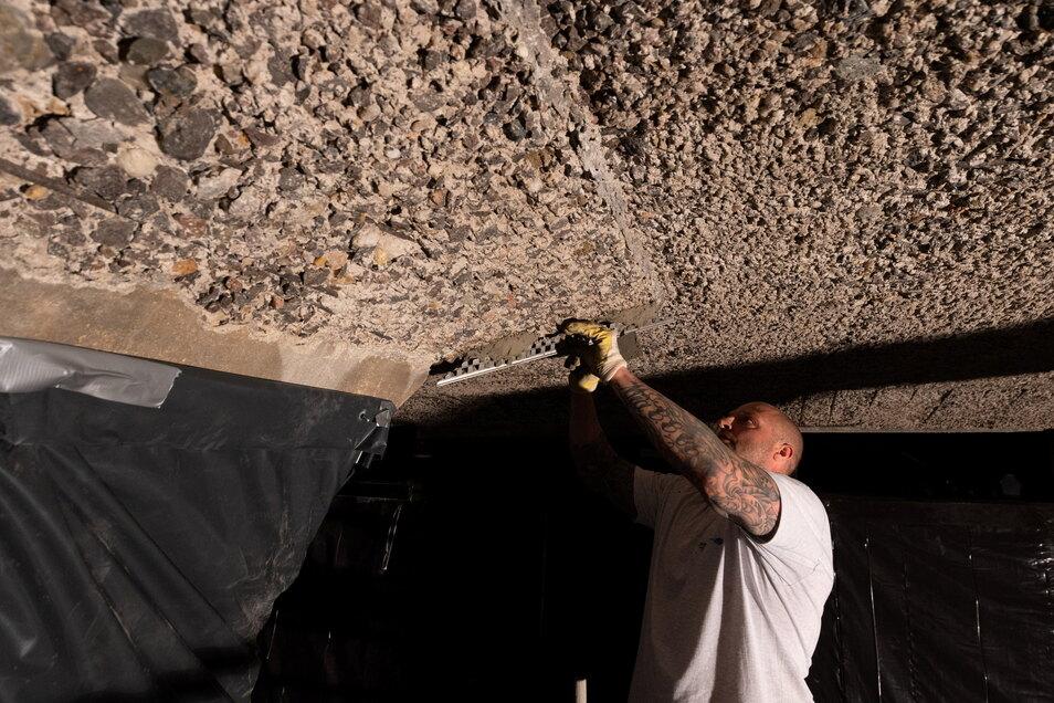 Sven Huck bereitet die neue Beschichtung der Decke vor. Der 42-jährige Betonsanierer bringt an den Köpfen der Säulen Metallschinen an. Nur so ist es möglich, wieder ordentliche Kanten herzustellen.