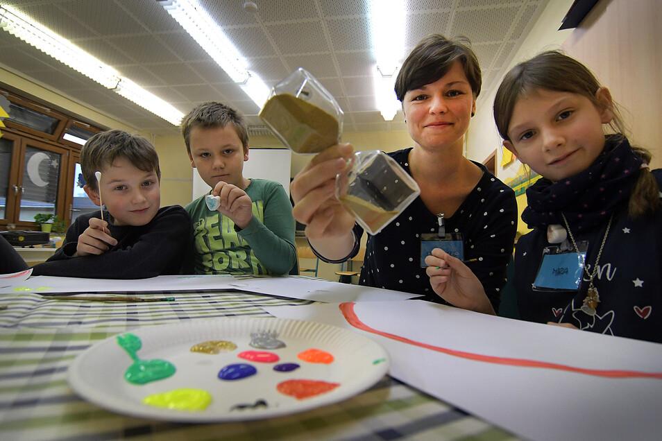 """Danielle Bennemann (2.v.r.) vom Elternverein krebskranker Kinder symbolisiert mit der Sanduhr, dass die Zeit vergeht. Tristan, Paul und Mira (v.l.) nehmen an dem einwöchigen Projekt """"Hospiz macht Schule"""" teil."""