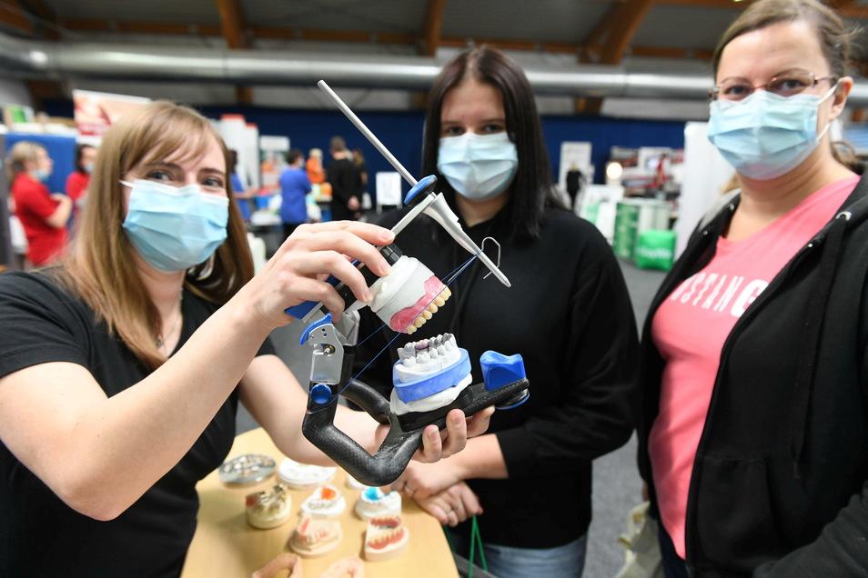 Bianca Bierig vom Dental-Studio Hartha erklärt Michèle und Nicole Haaser ihren Beruf als Zahntechnikerin anhand eines Modells.