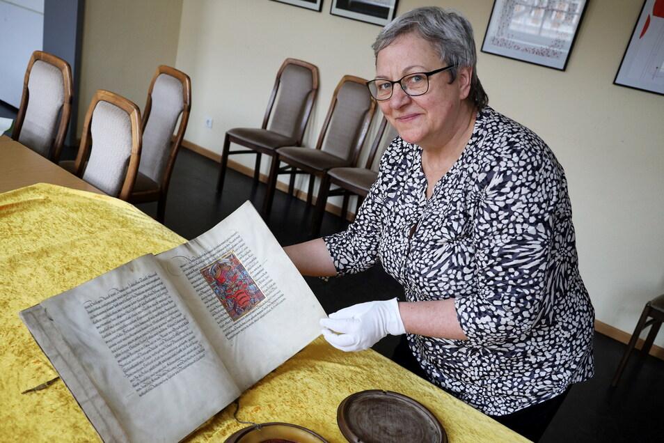 """Maritta Prätzel zeigt den Adelsbrief, auf den sie im Rahmen der Sendung """"Bares für Rares"""" aufmerksam wurde. Das Dokument wurde nun der Stadt Riesa vermacht - und am Eingang zum Stadtrat präsentiert."""