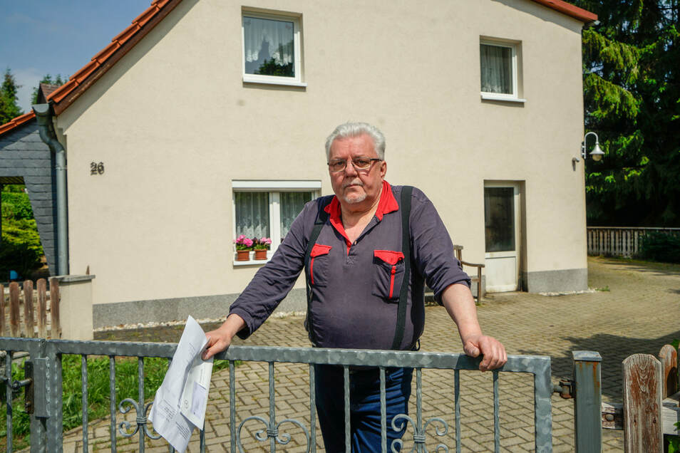 Roland Hornig steht am Zaun seines Grundstückes in Großharthau. In der Nacht zum Freitag wurde auf sein Haus ein Brandanschlag verübt. An der Tür rechts sind die Spuren deutlich zu sehen.