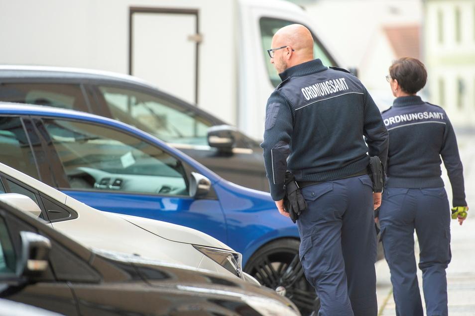 Ein Bild, wie es in Großenhain häufig zu sehen ist: Vollzugsbedienstete des städtischen Ordnungsamtes kontrollieren am Dienstagvormittag auf der Dresdner Straße, ob ein Parkschein gelöst worden ist.