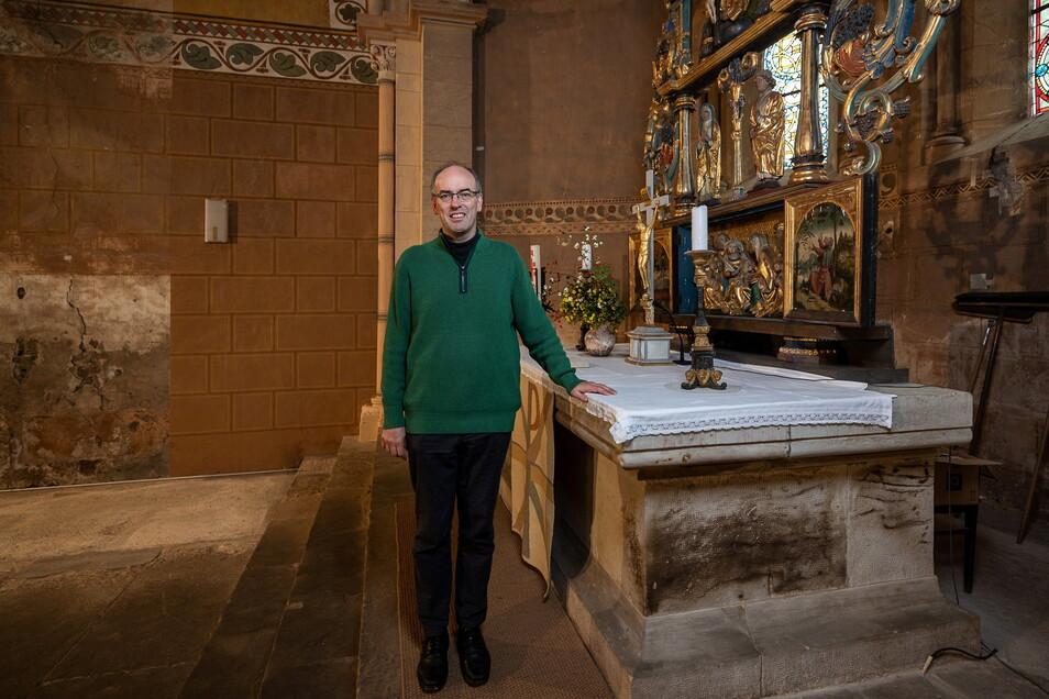 Pfarrer Sebastian Schurig steht am Altar der Nikolaikirche in Dippoldiswalde. Links von ihm an der Wand ist der Streifen zu erkennen, der zeigt, wie die Kirche nach einer Restaurierung aussehen kann.