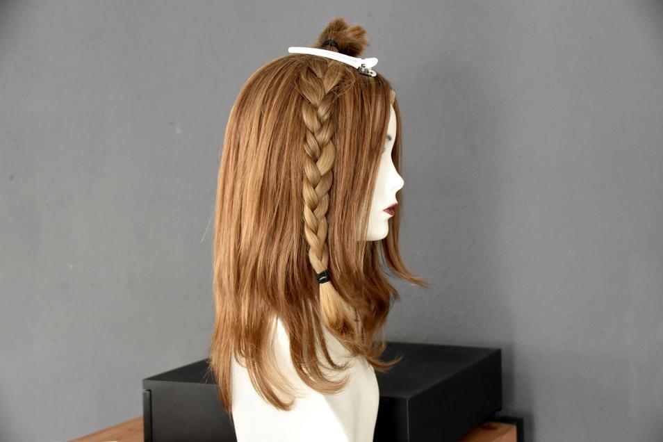 Echtes Haar zu echtem Haar: Ailas abgeschnittener Zopf hat fast die gleiche Farbe wie diese Perücke aus Spenderhaar.