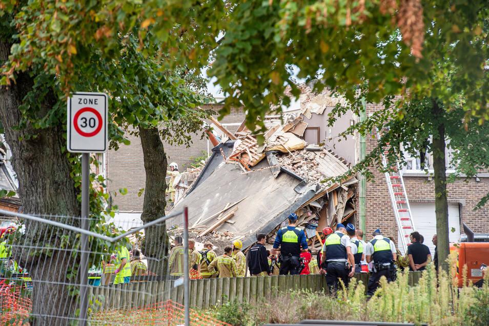 Rettungskräfte von Polizei und Feuerwehr stehen vor den Trümmern eines zerstörten Gebäudes.