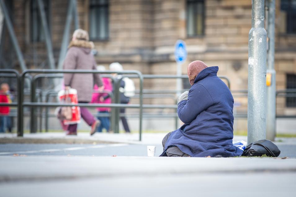 Ein Bettler wartet auf dem Pirnaischen Platz in Dresden darauf, dass Passanten Geld in seinen Becher werfen.