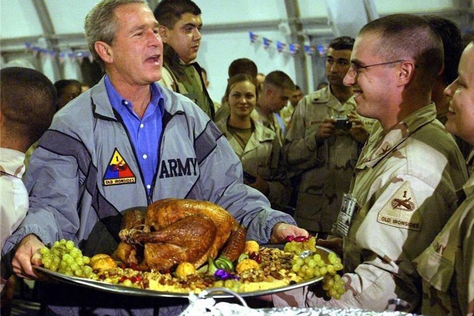 Eines der bekanntesten Fotos von Anja Niedringhaus: US-Präsident George W. Bush hält am 27. November 2003 auf dem Flughafen von Bagdad bei einem Thanksgiving-Essen mit etwa 600 Soldaten eine Platte mit einem Dekorations-Truthahn in Händen.