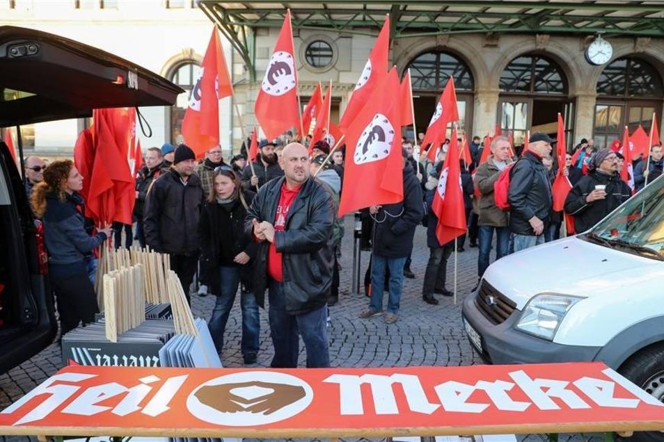 """Teilnehmer einer von der """"Merkeljugend"""" angemeldeten rechten Kundgebung auf dem Vorplatz des Hauptbahnhofs. Es sind Fahnen zu sehen, die an die Flaggen der NS-Zeit erinnern - mit einem schwarzen Euro-Symbol in einem weißen Kreis auf rotem Grund."""