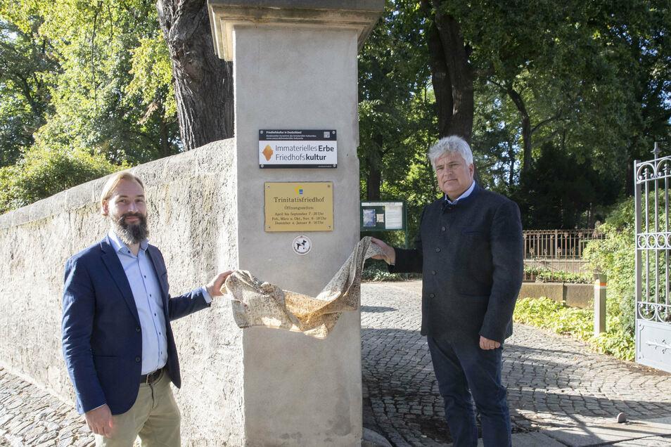 Pfarrer Martin Scheiter und Friedhofsverwalter Andreas Wolf enthüllen die Plakette am Eingang zum Trinitatisfriedhof.