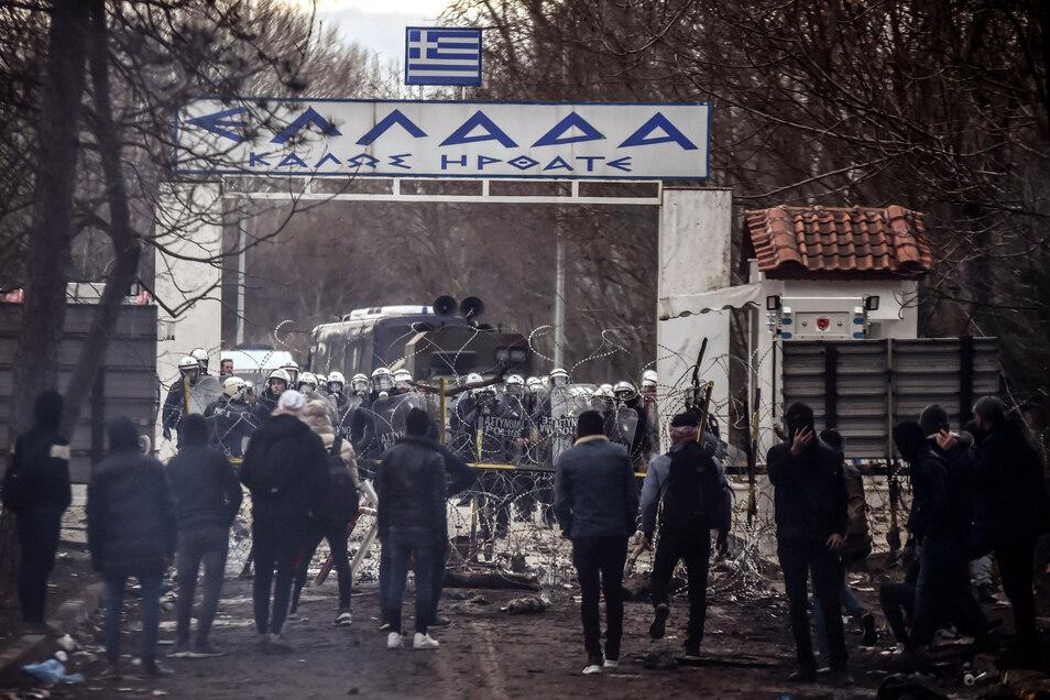 Griechische Grenzschützer stehen hinter einer Absperrung gegenüber Migranten, die versuchen, am Grenztor von Pazarkule nach Griechenland einzureisen.