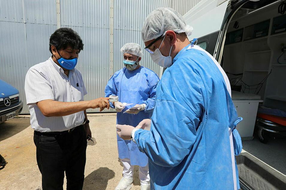 Evo Morales (l), Ex-Präsident von Bolivien (2006-2019), wird auf dem Flughafen El Palomar einem letzten Gesundheitscheck unterzogen, bevor er die Heimatreise aus dem argentinischen Exil antritt.