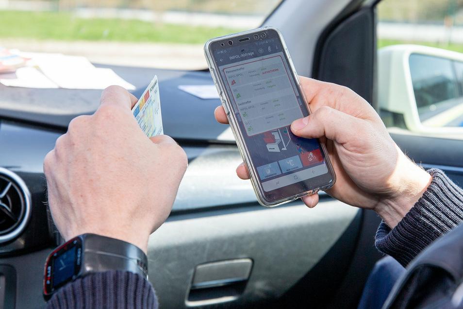 Die Bundespolizei prüft Dokumente per App auf einem Smartphone.