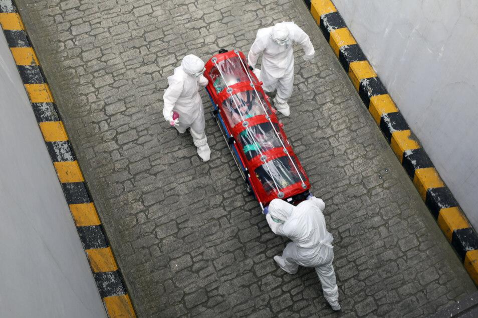 Medizinisches Personal beim Transport einer Patientin mit dem Coronavirus.