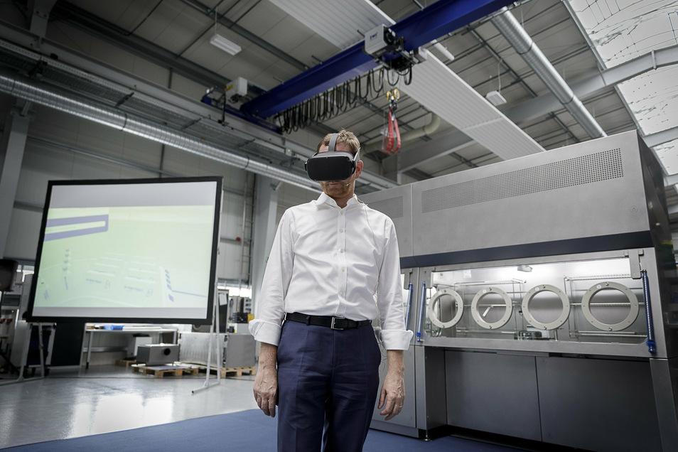 Michael Kretschmer beim Besuch des Maschinen- und Anlagenbauers SKAN in Görlitz. Im Hintergrund einer der modernen Isolatoren und die Videoleinwand, wo man sieht, wie Kretschmer virtuell hantiert.