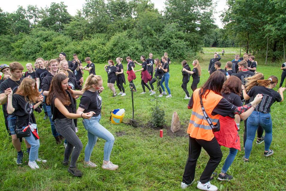 """Nach dem Pflanzen ging es ausgelassen zu: Die Abiturienten tanzten eine """"Annemarie-Polka"""" um die frisch gepflanzte Stechpalme."""