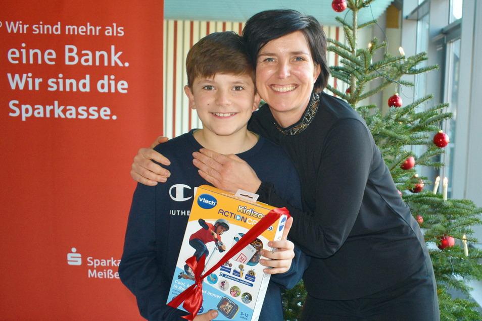 Tom Rabe kann sich über ein vorgezogenes Weihnachtsgeschenk freuen: Der Riesaer gewann bei der Sparkasse eine Kamera; im Bild mit seiner Mutter.