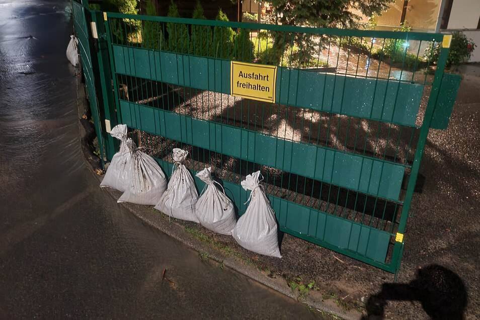 Mit Sandsäcken versucht die Familie das Grundstück am Abend vor der braunen Brühe zu schützen.
