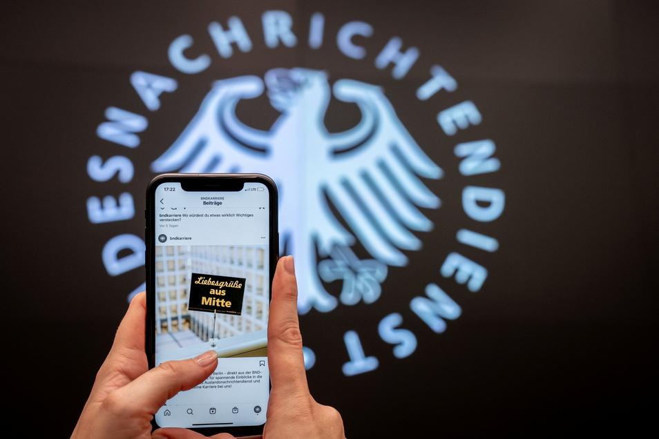 """Eine Mitarbeiterin zeigt in der Zentrale des Bundesnachrichtendienstes ein Foto mit einer Postkarte mit der Aufschrift """"Liebesgrüße aus Mitte"""". Das Foto wird einer der ersten Instagram-Posts des deutschen Auslandsgeheimdienstes."""