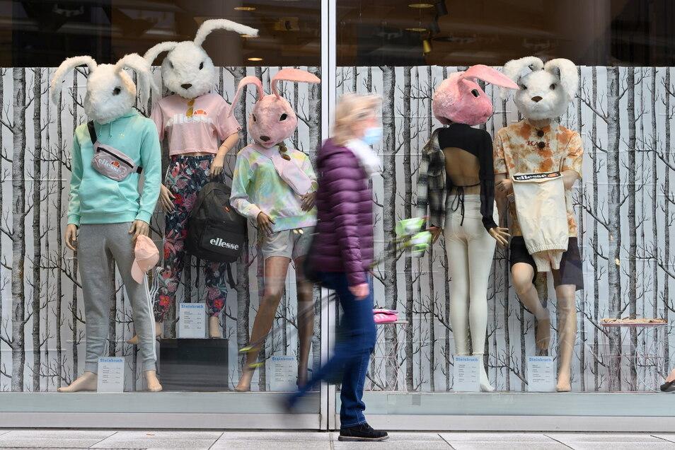 Eine Passantin geht an als Osterhasen verkleideten Modepuppen in einem Schaufenster eines Bekleidungsgeschäfts in Dresden vorbei.