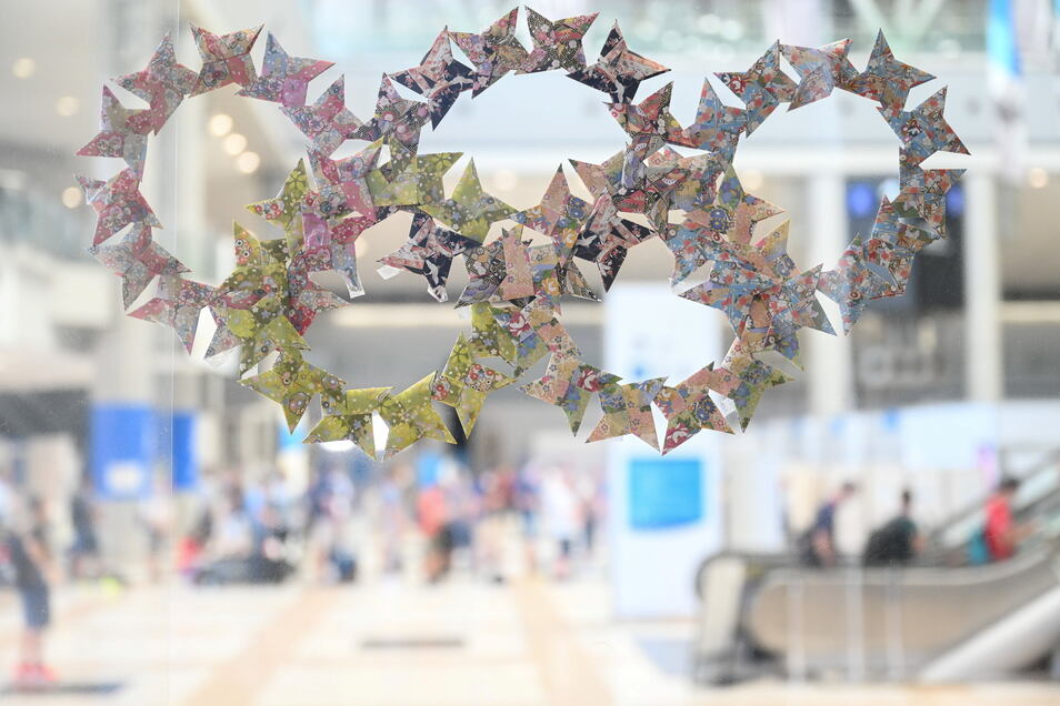 Tokio: Olympische Ringe aus Origamisternen hängen an einer Plexiglaswand.
