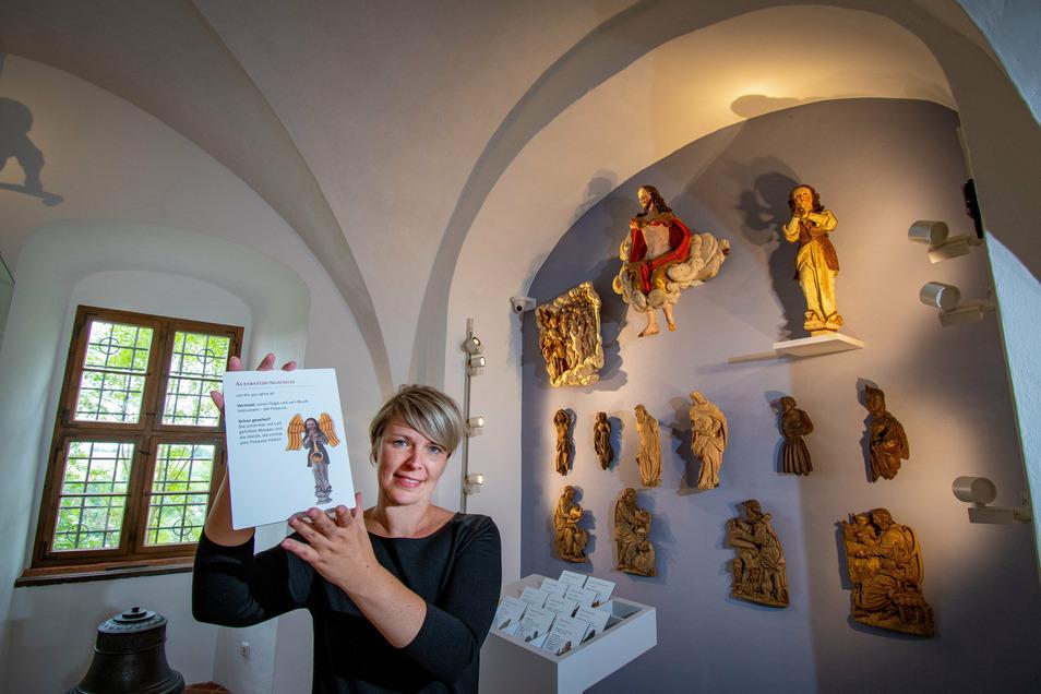 """In der Dauerausstellung """"Himmlische Helden"""" im Aktengewölbe der Burg Mildenstein zeigt Museologin Claudia Fischer eine Platte mit dem kompletten Auferstehungsengel. Im Original (rechts oben) ist er nicht mehr vollständig."""