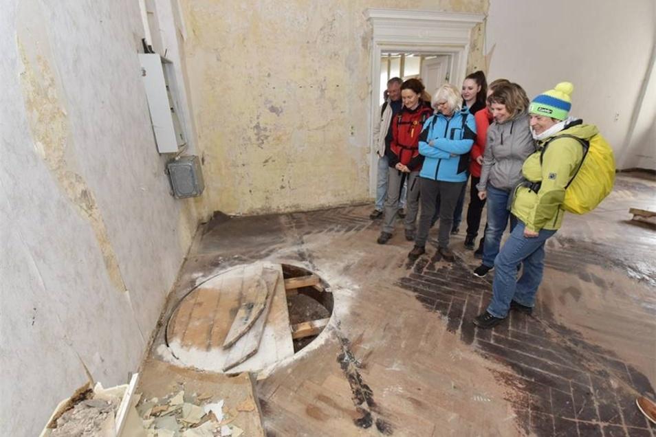 Eine Wandergruppe steht vor der runden Öffnung, durch die einst die Hexentreppe geführt hat. Kinder, die früher im Schloss lebten, haben sie so genannt, weil sie diese nicht betreten durften.