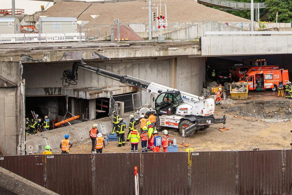Einsatzkräfte helfen bei der Bergungsarbeit an einer Tunnelbaustelle. Starker Regen hat am Freitag auf einer Tunnelbaustelle in Stuttgart einen schweren Unfall ausgelöst.