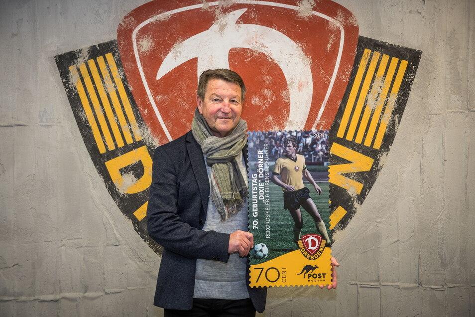 """Dynamos Ehrenspielführer Hans-Jürgen """"Dixie"""" Dörner präsentiert die Sonderbriefmarke, mit der er zum 68. Vereinsgeburtstag gewürdigt wird."""