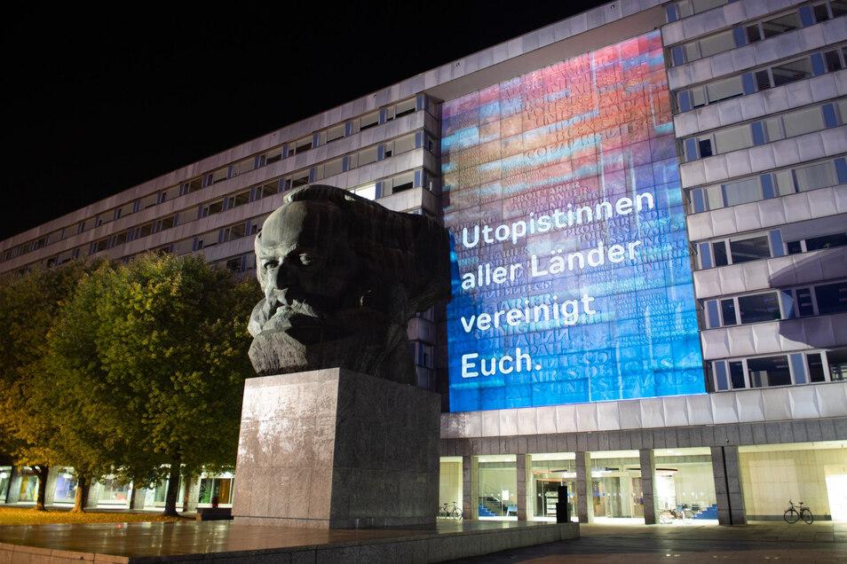 """Eine Lichtkunstinstallation mit der Aufschrift """"Utopistinnen aller Länder vereinigt euch"""" wird hinter dem Karl-Marx-Monument an die Fassade eines Wohnhaus projiziert. Anlass ist das bevorstehende Festival """"Aufstand der Utopien""""."""