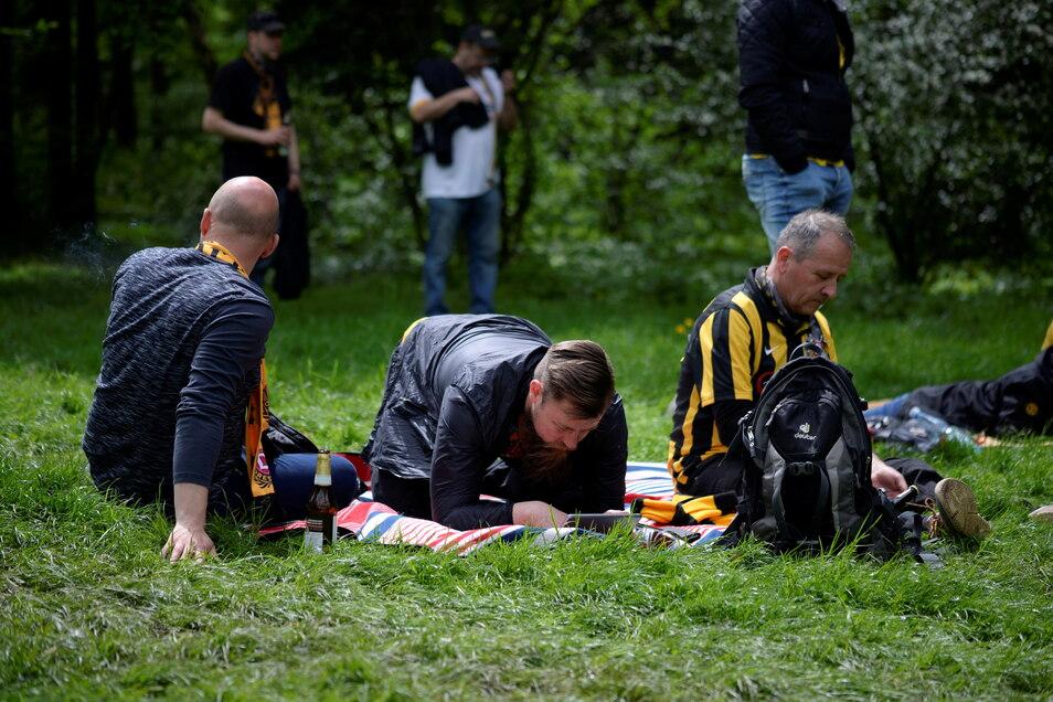 Viele Dynamo-Anhänger liegen friedlich im Gras und versuchen, das Spiel auf ihren Tablets und Handys zu verfolgen.