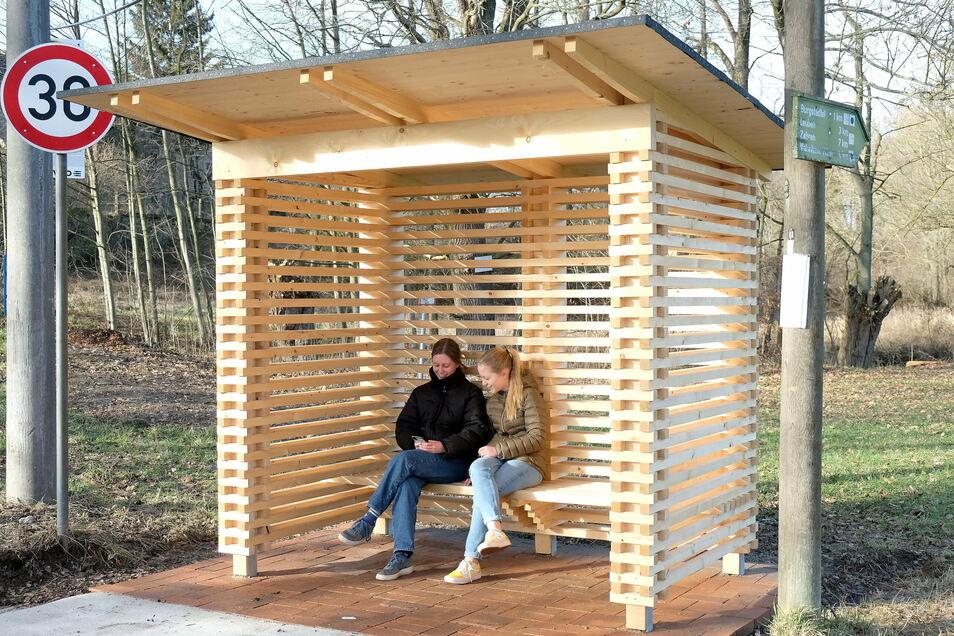 Das neue von Bürgern gebaute Holzhäuschen im Nossener OT Graupzig bietet den Schülerinnen Florentine und Luisa Schutz, wenn sie auf den Bus nach Nossen warten.