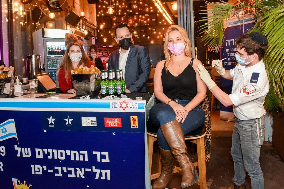 Eine junge Frau wird in Tel Aviv in einer Bar im Zentrum der Stadt geimpft. Die Stadtverwaltung von Tel Aviv bietet jedem, der sich dort impfen lässt, ein Freigetränk an.