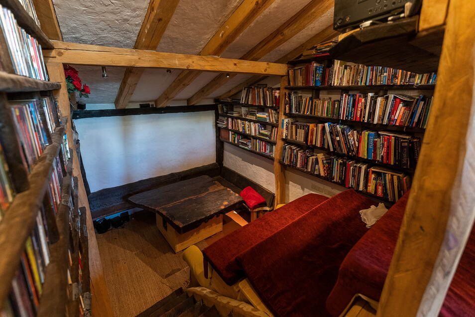 Das Wohnzimmerkino ist groß genug für zehn Leute, die Leinwand ganz unten. Rechts und links stehen die Bücher- und DVD-Sammlungen.