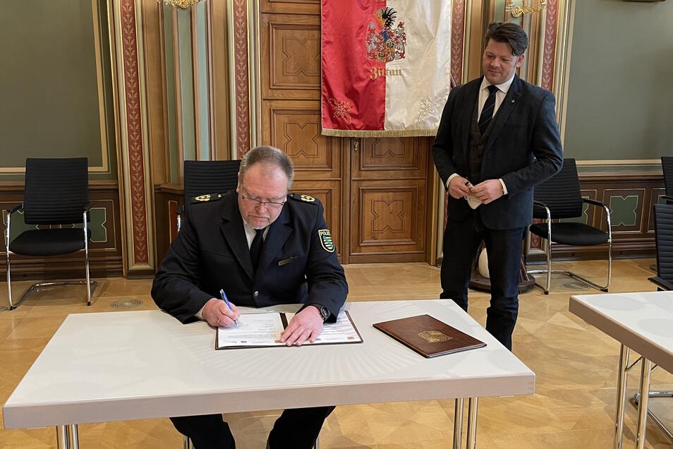 Polizeipräsident Manfred Weißbach beim Unterzeichnen der Vereinbarung. Neben ihm Zittaus Oberbürgermeister Thomas Zenker.