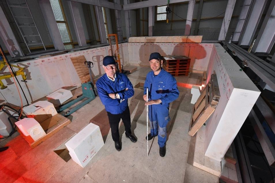 Dort, wo Geschäftsführer Hans-Bernhard Führ (l.) und Produktionsleiter André Novak stehen, blubbert künftig eine rund 1 400 Grad Celsius heiße Glasmasse. Novak zeigt an, wie hoch sie künftig im Ofen steht.