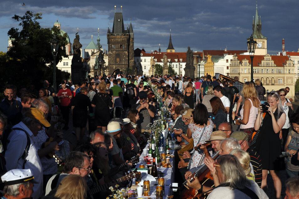 Eng beisammen, ohne Maske, ausgelassen feiernd. Am 30. Juni feiern Tschechen auf der Prager Karlsbrücke an einem 500 Meter langen Tisch das Ende der Corona-Maßnahmen.