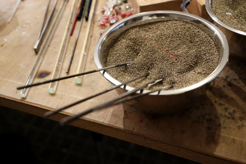 Die Werkstücke am Ende des Edelstahlstabs kühlen in einem Kühlgranulat ab.