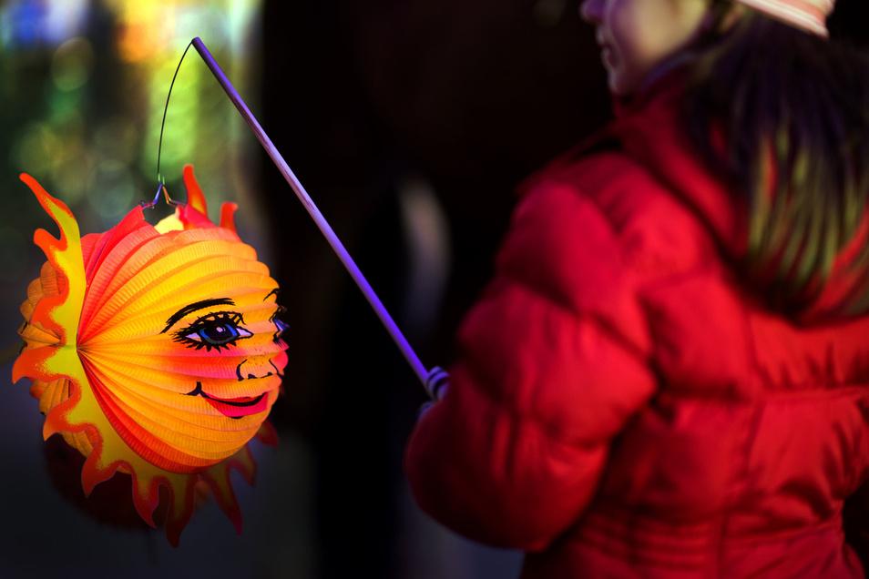 Ein Mädchen hält während eines Lampionumzuges im Rahmen des ökumenischen Martinsfestes eine Laterne in den Händen. Zum Gedenken an den heiligen Martin gehen Kinder alljährlich in der Zeit um den 11. November mit Laternen durch die Straßen.