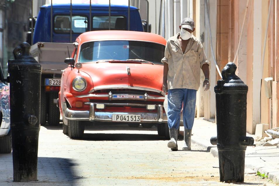 Ein Mann mit Mund-Nasen-Schutz geht auf einer Straße durch Havanna. Kuba setzt einen eigenen Impfstoff gegen Corona ein.