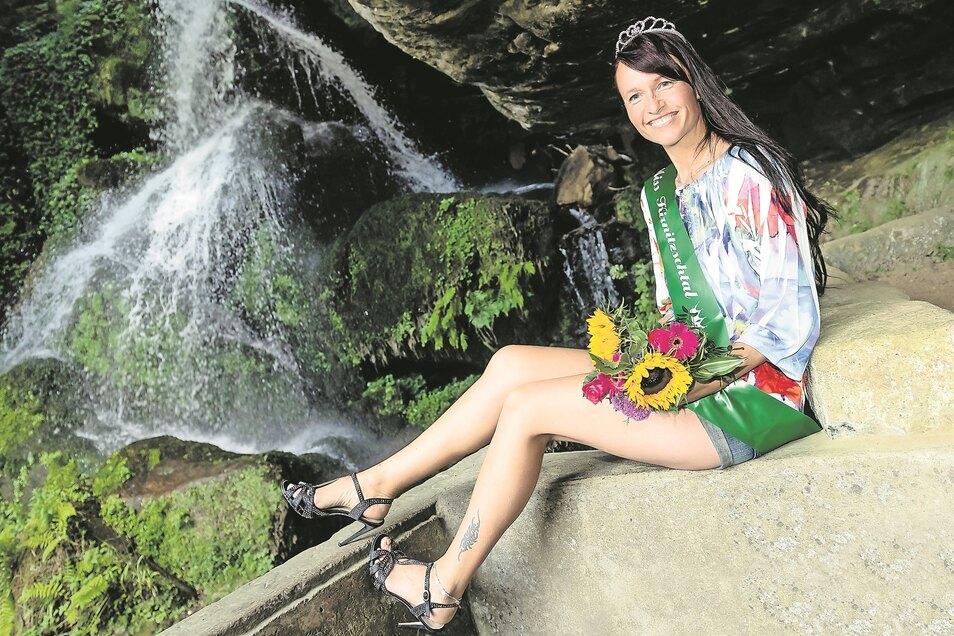 Die 39-jährige Manuela mit Krönchen und Schärpe vor dem Lichtenhainer Wasserfall. Kurz vor 17 Uhr war sie am Samstag zur schönsten Frau des Kirnitzschtals gewählt worden.