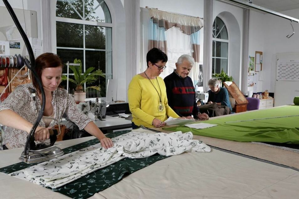 Auf einem riesigen Tisch wird der Stoff für die Kinopaläste zurechtgeschnitten. Cornelia Kloß (Mitte) leitet den Raumausstatterbetrieb, den ihr Vater Waldemar (rechts) vor 53 Jahren gegründet hat. Katrin Polawski (links) bügelt Gardinenstoff.