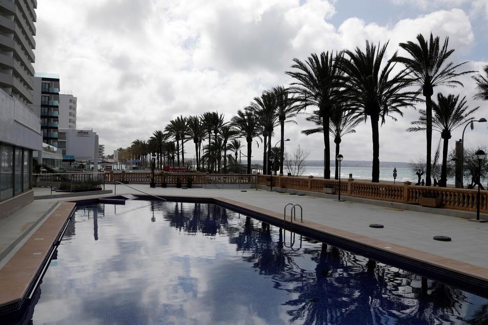 Palmen spiegeln sich im Pool eines geschlossenen Hotels am Strand von Arenal.