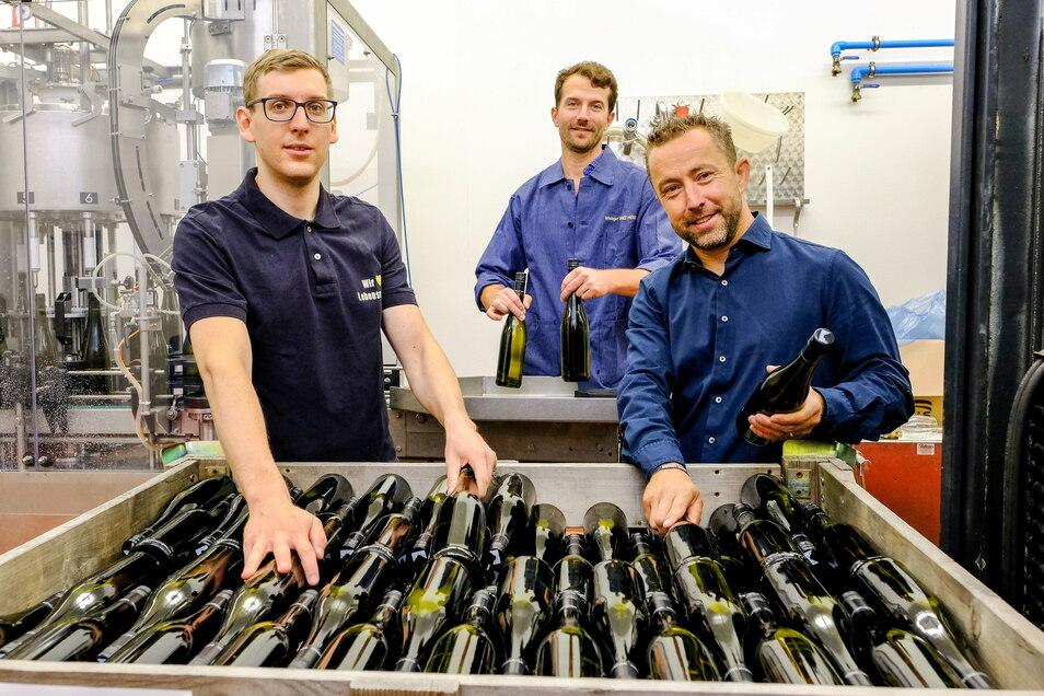 Im Weingut Drei Herren füllten Azubi Kevin Grune (v.l.n.r.) mit Kellermeister Jacob Wiedemann und Edeka-Marktinhaber John Scheller den Wein in Flaschen ab.
