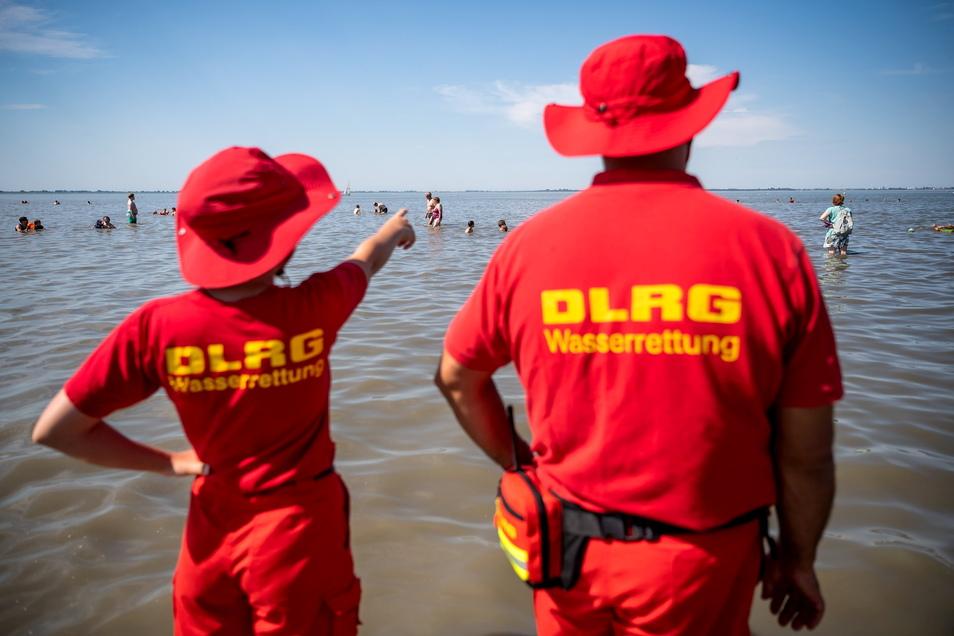 Mitglieder der DLRG (Deutsche Lebens-Rettungs-Gesellschaft) stehen an einem Strand und beobachten Badende.