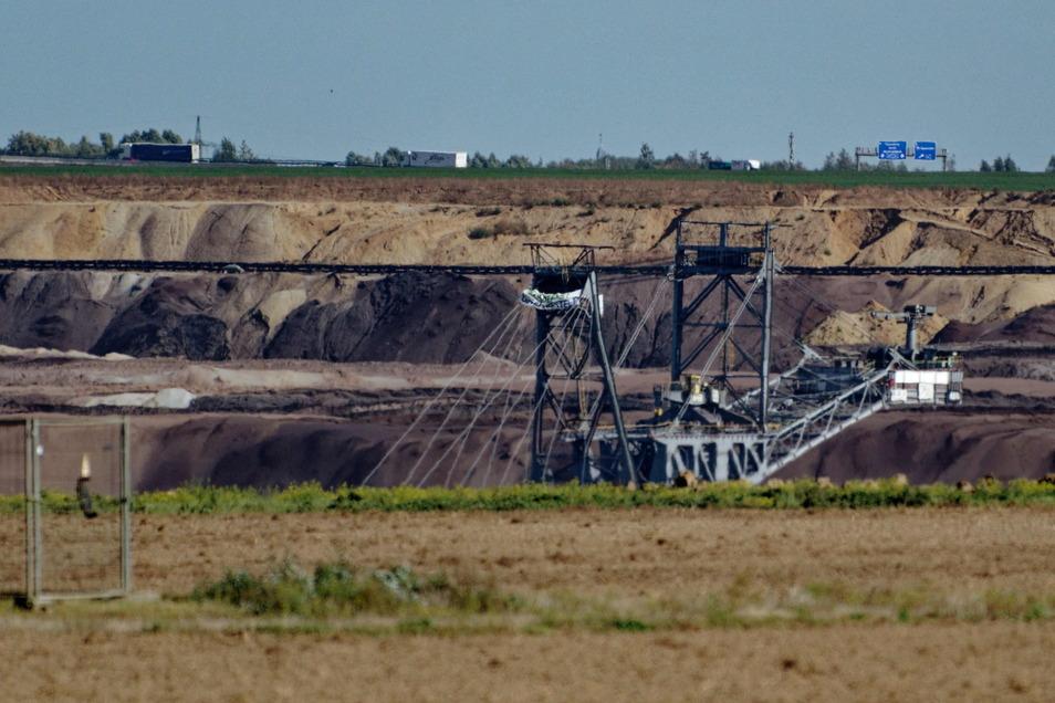 Die Spitze eines von Klimaaktivisten besetzen Baggers ragt aus dem Tagebau Garzweiler II.